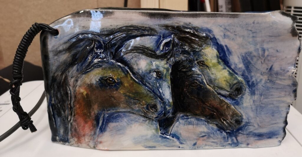 Ceramic vase with carved horses painted with slip.